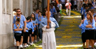 A priest is carrying a cross down the flowered streets of Cagli. Behind him are scouts. The scouts come early to help decorate the streets in honor of the procession.