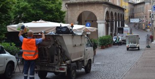 Workers of Marche Multiservizi clean the streets of Urbino by disposing filled trash bins before the town awakens.