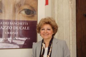 Maria Claudia Caldari poses in front of La Muta advertisement outside the Palazzo Ducale.