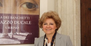 Maria Claudia Caldari poses in front of La Muta advertisement outside the Palazzo Ducale.