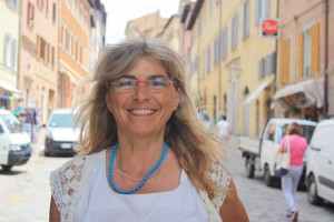 Maria Giovanna Luminati stands under the arch entering Urbino, proudly welcoming guests and visitors.