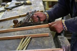 Domenico shaving a freshly cut piece of wood.
